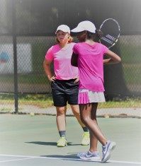 Coach Grace helping a player with her backhand groundstroke